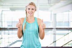 Усмехаясь белокурые большие пальцы руки положения и показа вверх стоковая фотография