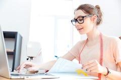 Усмехаясь белошвейка женщины работая с компьтер-книжкой в студии Стоковая Фотография