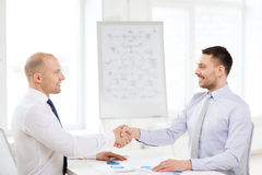 2 усмехаясь бизнесмена тряся руки в офисе Стоковая Фотография