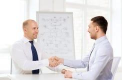 2 усмехаясь бизнесмена тряся руки в офисе Стоковые Фото