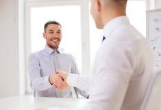 2 усмехаясь бизнесмена тряся руки в офисе Стоковое Изображение RF