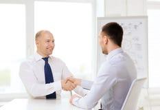2 усмехаясь бизнесмена тряся руки в офисе Стоковое фото RF