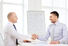 2 усмехаясь бизнесмена тряся руки в офисе Стоковые Изображения