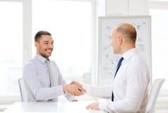 2 усмехаясь бизнесмена тряся руки в офисе Стоковые Фотографии RF