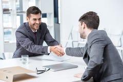 2 усмехаясь бизнесмена тряся руки на встрече в офисе Стоковая Фотография