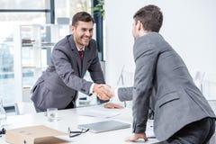 2 усмехаясь бизнесмена тряся руки на встрече в офисе Стоковые Изображения