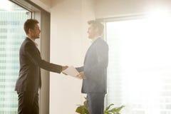 2 усмехаясь бизнесмена тряся руки пока стоящ в солнечном  Стоковое фото RF
