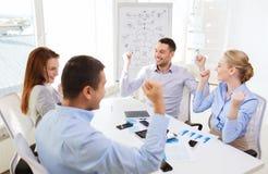 Усмехаясь бизнесмены встречая в офисе Стоковые Изображения RF