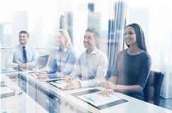 Усмехаясь бизнесмены встречая в офисе Стоковые Изображения