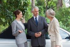 Усмехаясь бизнесмены говоря совместно первоклассным cabriolet Стоковые Изображения