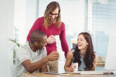 Усмехаясь бизнесмены держа кофейные чашки на столе компьютера Стоковая Фотография RF