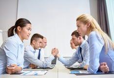 Усмехаясь бизнесмены имея конфликт в офисе Стоковая Фотография RF
