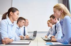 Усмехаясь бизнесмены имея конфликт в офисе Стоковые Фотографии RF