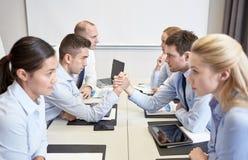 Усмехаясь бизнесмены имея конфликт в офисе Стоковые Фото