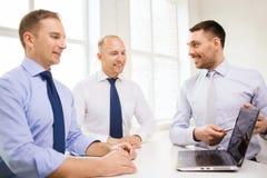 Усмехаясь бизнесмены имея обсуждение в офисе Стоковые Фото