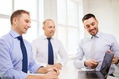 Усмехаясь бизнесмены имея обсуждение в офисе Стоковые Изображения