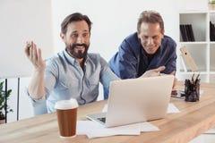 Усмехаясь бизнесмены используя компьтер-книжку и выпивая кофе от бумажного стаканчика в офисе Стоковые Фото