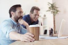 Усмехаясь бизнесмены используя компьтер-книжку и выпивая кофе от бумажного стаканчика в офисе Стоковая Фотография