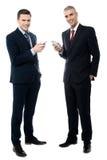 Усмехаясь бизнесмены используя мобильный телефон стоковое фото