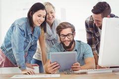 Усмехаясь бизнесмены используя цифровую таблетку на столе компьютера Стоковые Изображения RF