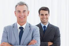 Усмехаясь бизнесмены представляя смотрящ камеру Стоковая Фотография RF