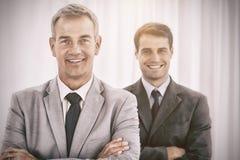 Усмехаясь бизнесмены представляя смотрящ камеру Стоковое фото RF