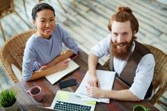 Усмехаясь бизнесмены работая в современном офисе Стоковые Изображения RF