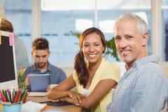 Усмехаясь бизнесмены работая в творческом офисе с работниками Стоковое Фото