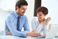 Усмехаясь бизнесмены работая совместно в офисе Стоковое фото RF