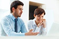 Усмехаясь бизнесмены работая совместно в офисе Стоковое Изображение RF