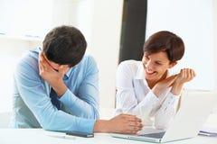 Усмехаясь бизнесмены работая совместно в офисе Стоковые Фотографии RF