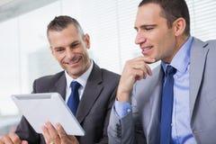 Усмехаясь бизнесмены работая совместно на их таблетке Стоковые Фотографии RF
