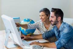Усмехаясь бизнесмены работая совместно на компьютере Стоковое Изображение