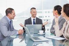 Усмехаясь бизнесмены работая совместно над кофе Стоковое Фото