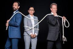 Усмехаясь бизнесмены связывая зрелую азиатскую коммерсантку с веревочкой Стоковые Изображения