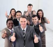 Усмехаясь бизнесмены смотря камеру и показывая большие пальцы руки вверх Стоковые Фото