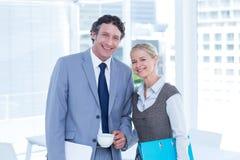 Усмехаясь бизнесмены смотря камеру Стоковая Фотография
