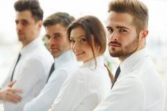Усмехаясь бизнесмены стоя совместно в линии в современном  Стоковое Изображение