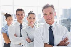 Усмехаясь бизнесмены стоя совместно в линии Стоковая Фотография