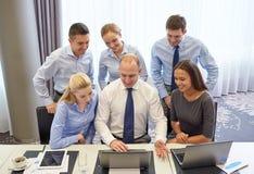 Усмехаясь бизнесмены с компьтер-книжкой в офисе Стоковые Изображения RF