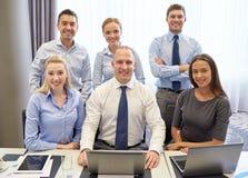 Усмехаясь бизнесмены с компьтер-книжкой в офисе Стоковое Изображение RF