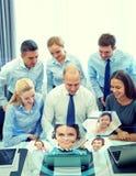 Усмехаясь бизнесмены с компьтер-книжкой в офисе Стоковое фото RF
