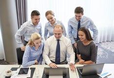Усмехаясь бизнесмены с компьтер-книжкой в офисе Стоковая Фотография RF