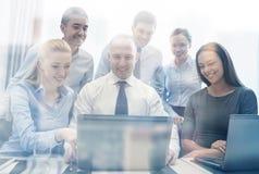 Усмехаясь бизнесмены с компьтер-книжкой в офисе Стоковые Фото