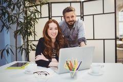 Усмехаясь бизнесмены с компьтер-книжкой на столе Стоковое Фото
