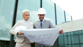 Усмехаясь бизнесмены с светокопией и шлемами Стоковое Изображение RF