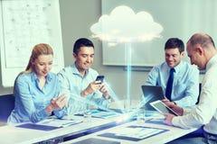 Усмехаясь бизнесмены с устройствами в офисе Стоковые Фотографии RF