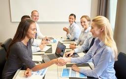 Усмехаясь бизнесмены тряся руки в офисе Стоковая Фотография