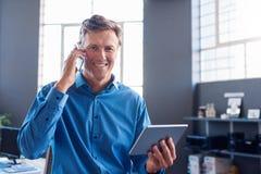 Усмехаясь бизнесмен говоря на его мобильном телефоне и использовании таблетки Стоковые Изображения RF
