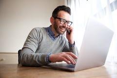 Усмехаясь бизнесмен говоря на мобильном телефоне и работая на компьютере Стоковое Изображение RF